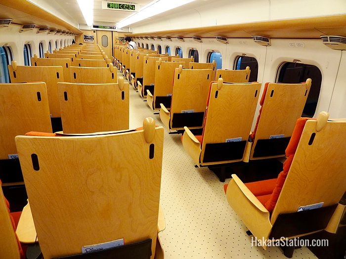 Interior design elements of the Kyushu Shinkansen include wooden-backed seats and gold-leaf paneling