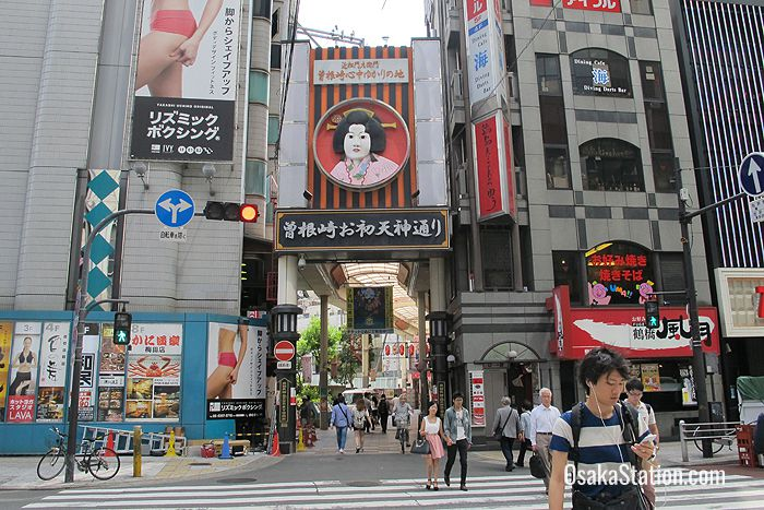 The face of the tragic heroine Ohatsu is shown above the entrance to Ohatsutenjin-dori Shotengai