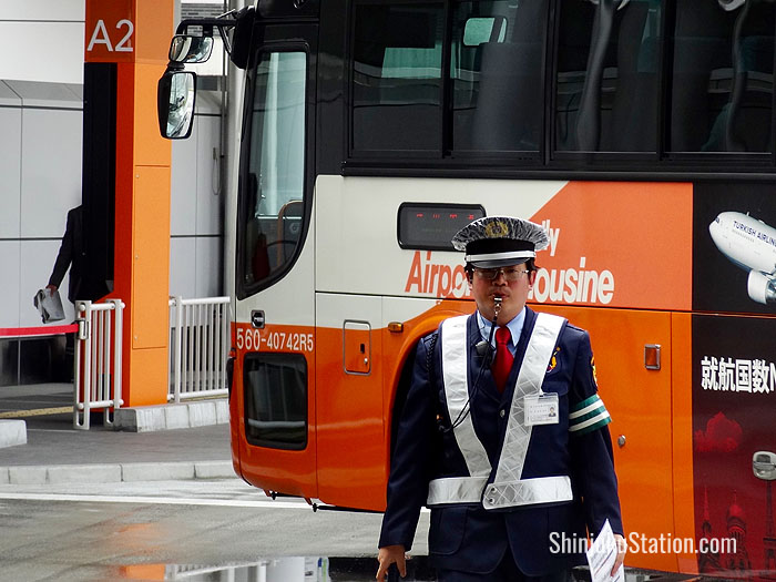 A bus parking agent sees off an airport shuttle at Basuta Shinjuku