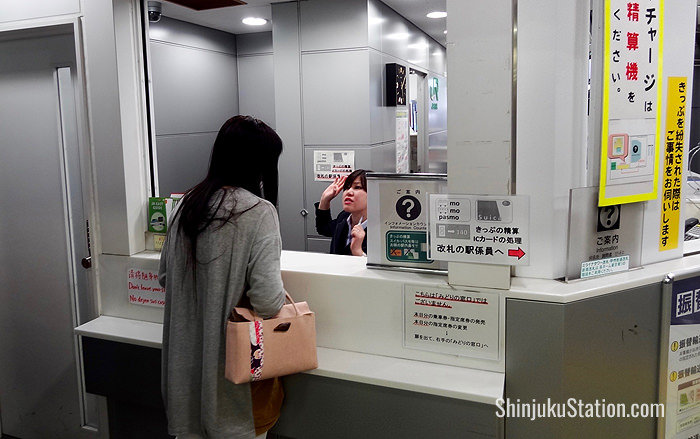 Staff at a booth by the South Exit ticket gates help direct passengers